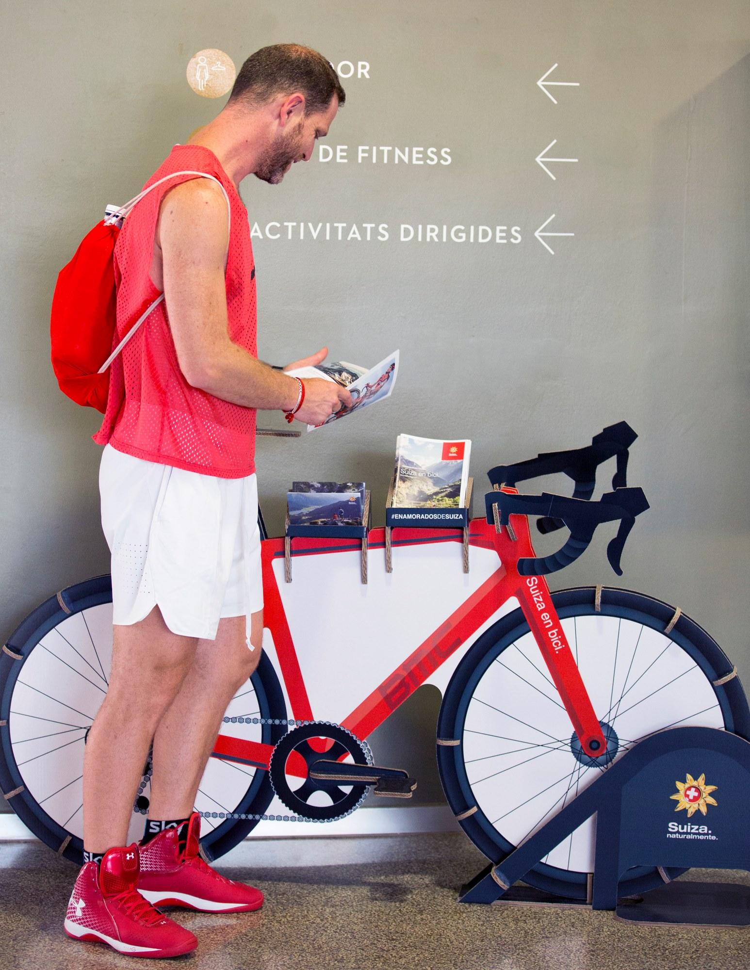 expositor portafolletos porta folletos bicicleta carton gimnasio holmes madrid barcelona oficina turismo suiza