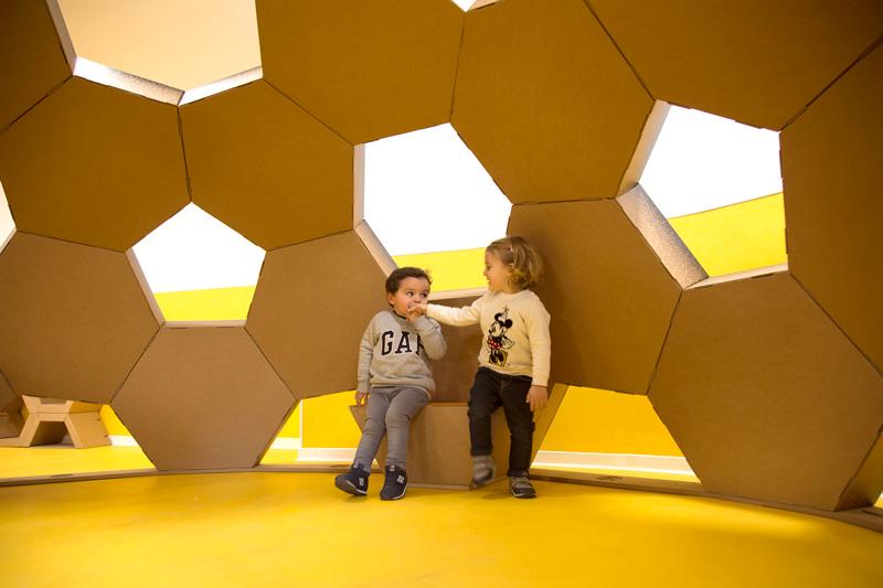 Cúpula geodésica de cartón desde dentro con niños interactuando