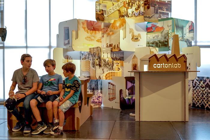 Niños sentados en el stand de Cartonlab