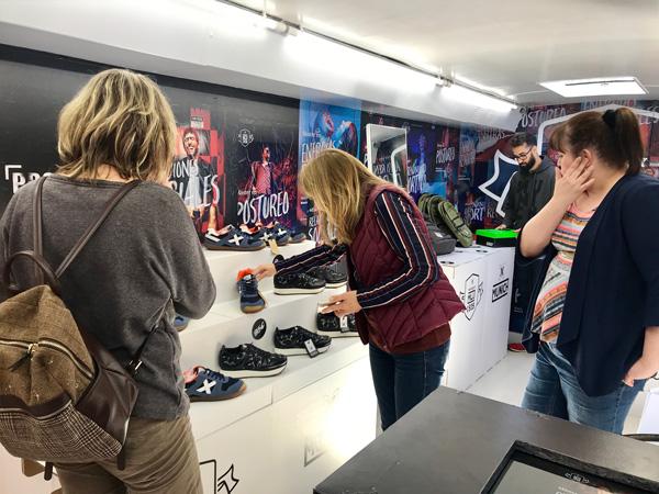 Jóvenes viendo las zapatillas Munich en expositor escalonado